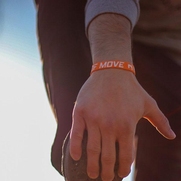 Oranžový náramek s parkour motivem u otírání bot